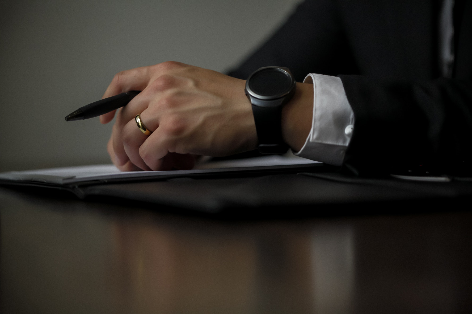 Close of up businessman's holding a pen, wearing a black watch and a gold wedding band