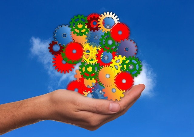 Hand holding a graphic of colorful gears and cogs, against a background of a blue sky with a single cloud
