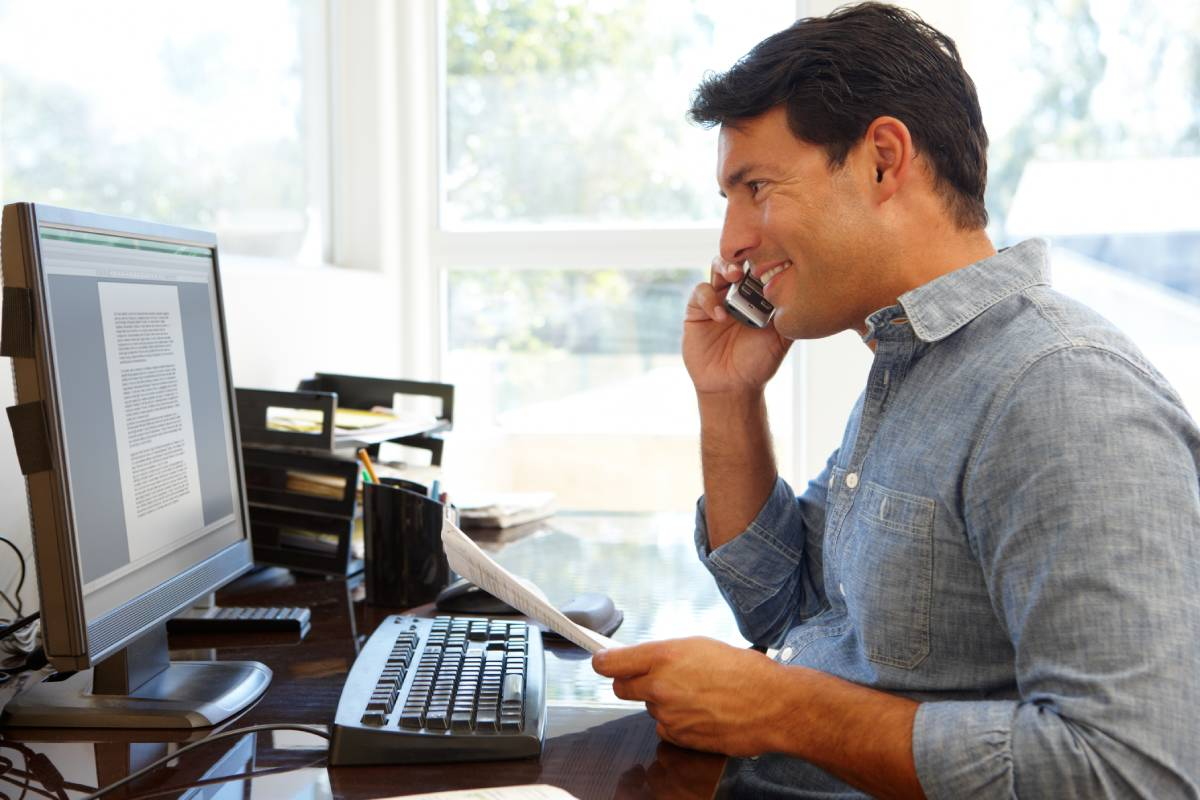 A man working from home using a computer while talking on the phone